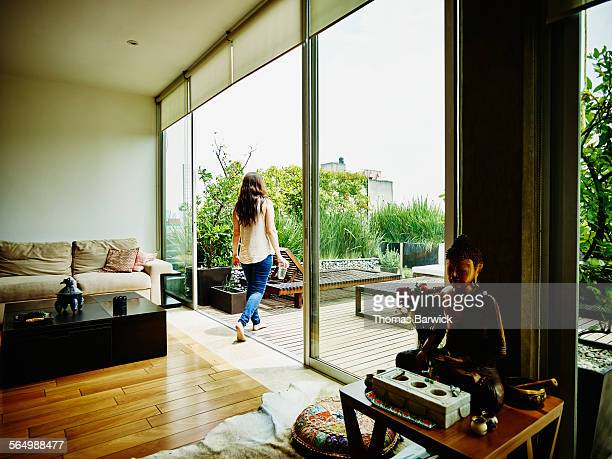 Woman walking out to rooftop garden patio