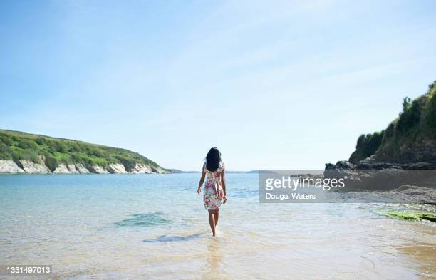 woman walking out to sea on idyllic beach. - one mid adult woman only stock pictures, royalty-free photos & images