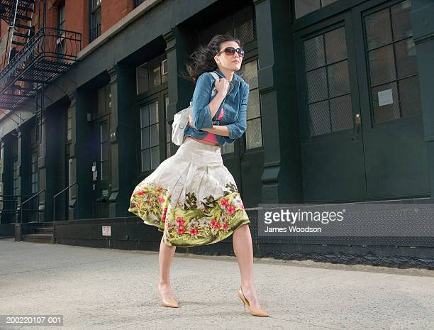 woman walking outdoors on pavement, hair blowing in wind - skirt blowing stock photos and pictures