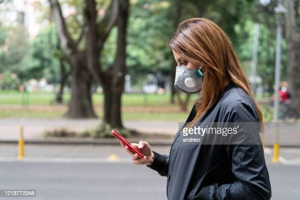 woman walking outdoors wearing a facemask to avoid corona virus - software foto e immagini stock