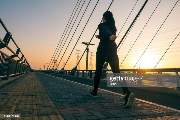 woman walking outdoors with sunlight - slow motion stock pictures, royalty-free photos & images