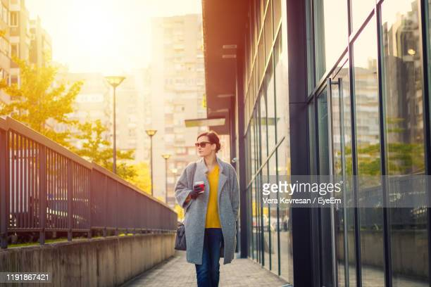 woman walking outside building in city - long coat stock pictures, royalty-free photos & images