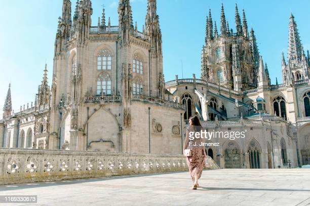 woman walking outside the cathedral of burgos - burgos stock-fotos und bilder
