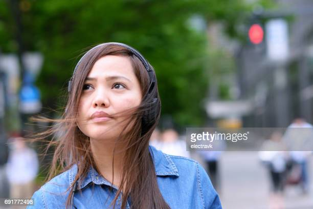 Woman walking outside with headphones on