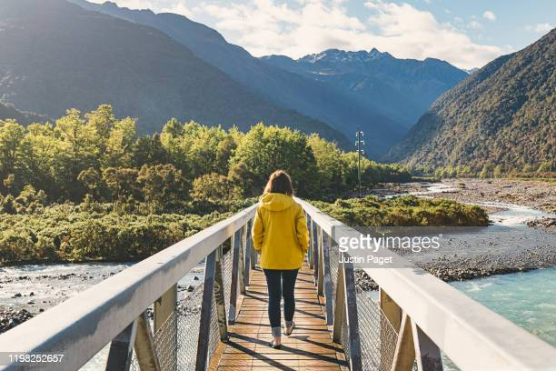 woman walking over bridge into mountains - canterbury region new zealand stock pictures, royalty-free photos & images