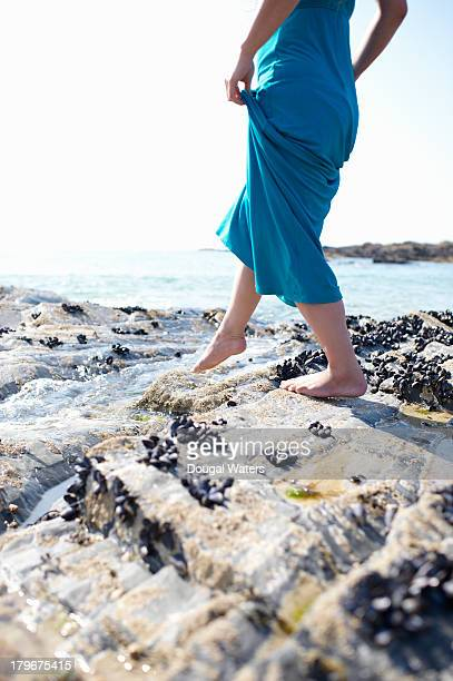 woman walking over coastal rocks. - long dress stock pictures, royalty-free photos & images