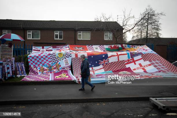 Woman walking past a display of home club flags on Harry Potts Way outside the stadium before Burnley hosted Everton in an English Premier League...