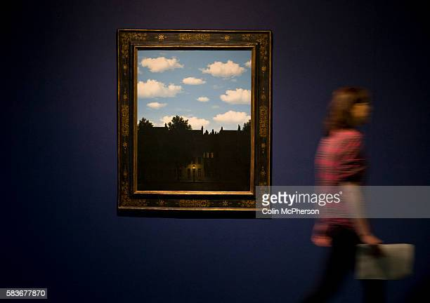 A woman walking past a painting entitled 'The Dominion of Light ' by Rene Magritte part of an exhibition of the artist's work which will open at Tate...