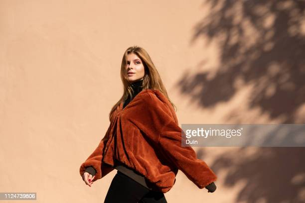woman walking past a wall with shadow of a tree - secteur de la mode photos et images de collection