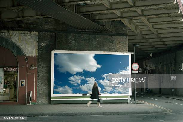Woman walking past billboard poster of cloudy sky on city street