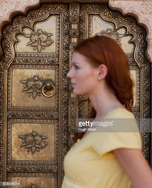 woman walking past ornate door - hugh sitton india stock pictures, royalty-free photos & images