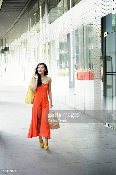 woman walking past shop windows with bags - orange dress stock pictures, royalty-free photos & images