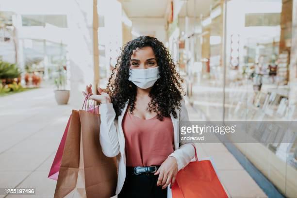 mujer caminando de compras y sonriendo detrás de la máscara - venta al por menor fotografías e imágenes de stock