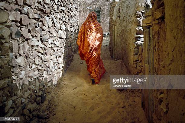 Woman walking stone paved alley