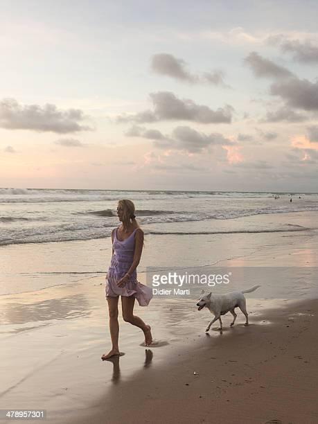 Woman walking the dog on the beach in Bali