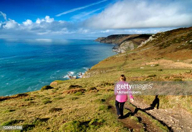 woman walking the south west coast path between salcombe and hope cove, devon - coastal feature stock pictures, royalty-free photos & images