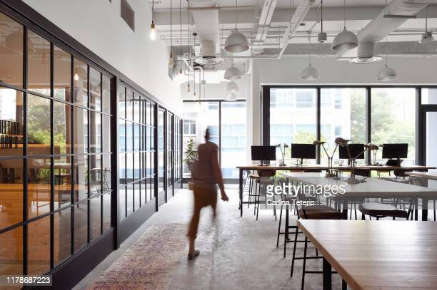 woman walking through a co-working office - open plan stock pictures, royalty-free photos & images