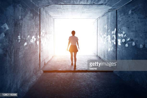 woman walking through a dark tunnel - escapism stock photos and pictures