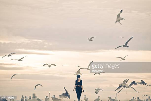 Woman walking through a flock of seagulls