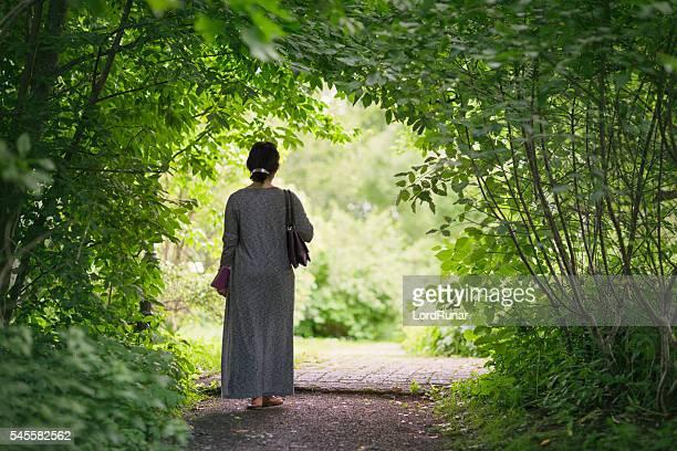 Woman walking through a green garden