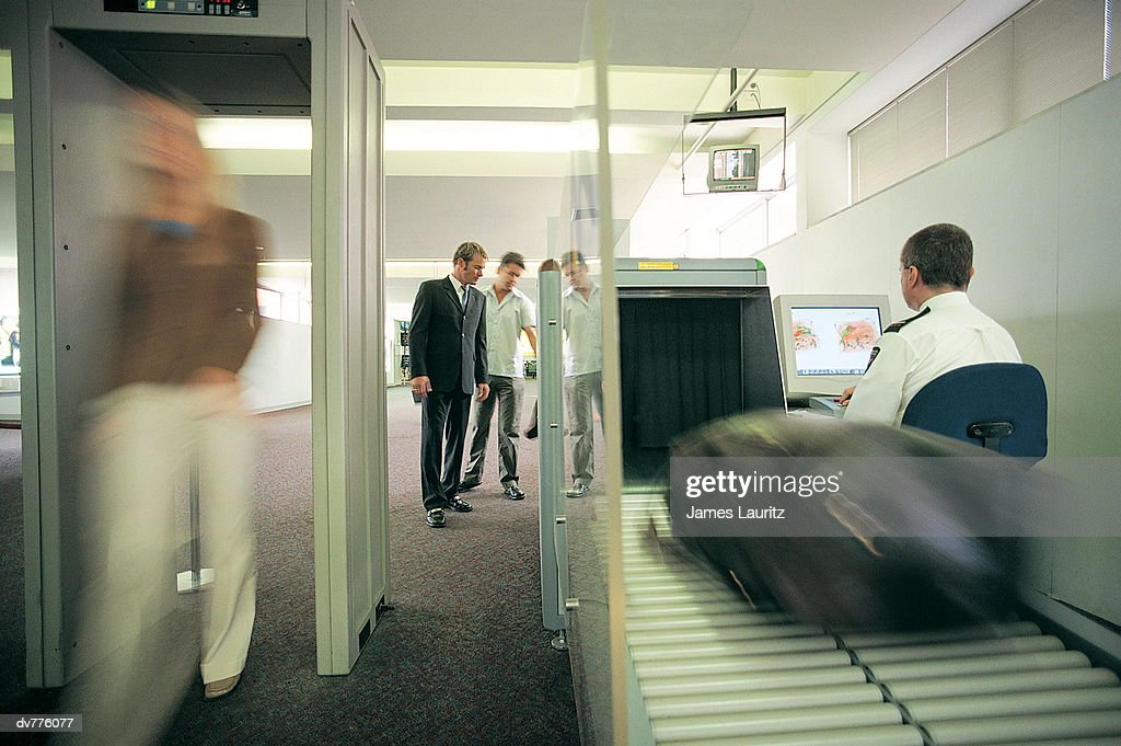 Woman Walking Through a Metal Detector as Her Baggage is X-Rayed at the Airport : Foto de stock