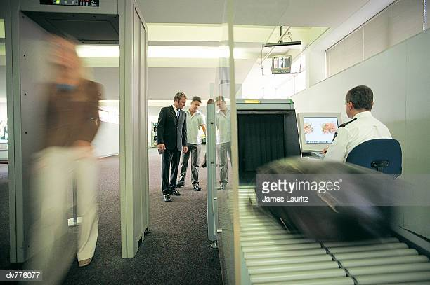woman walking through a metal detector as her baggage is x-rayed at the airport - security check - fotografias e filmes do acervo