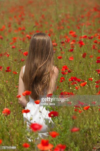 Woman walking through a poppy field, Bulgaria