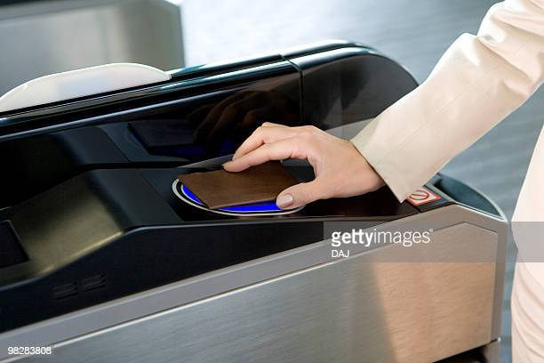 Woman walking through automatic ticket wicket at station, close up