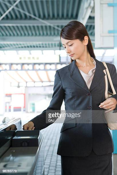 woman walking through automatic ticket wicket at station - 改札 ストックフォトと画像