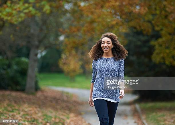 Woman walking through city park and smiling.