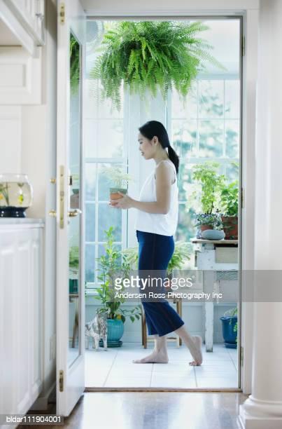Woman Walking Through Doorway with Plant