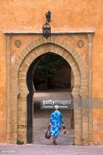woman walking through entrance to the kasbah des oudaias - rabat morocco stock pictures, royalty-free photos & images