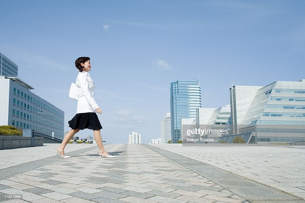 Woman walking through financial district : Stock Photo