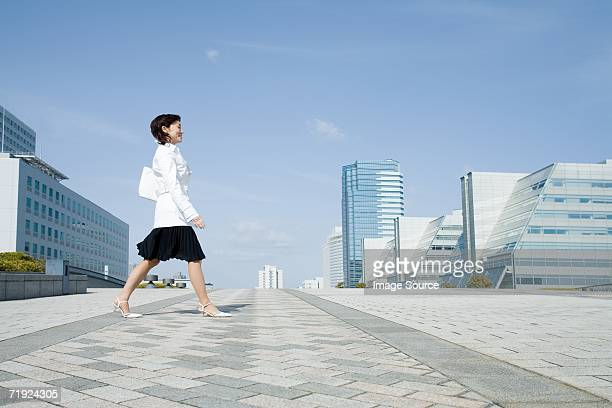 woman walking through financial district - striding stock pictures, royalty-free photos & images