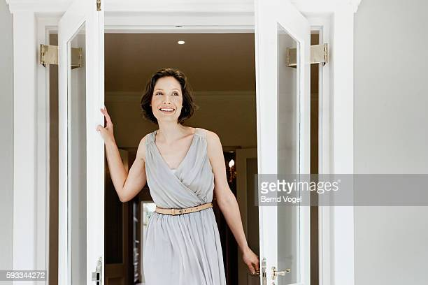 woman walking through french doors - belt stock pictures, royalty-free photos & images