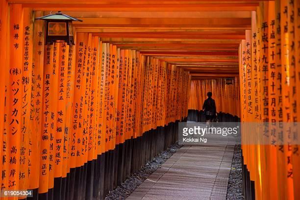 Woman walking through Fushimi Inari Shrine