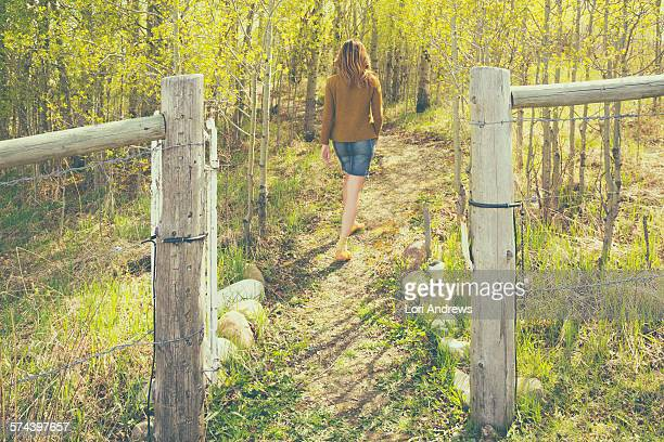 Woman walking through gate into forest