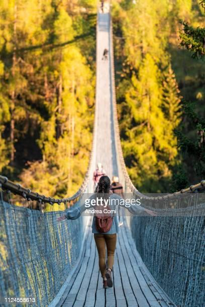 woman walking through goms bridge - hängebrücke stock-fotos und bilder