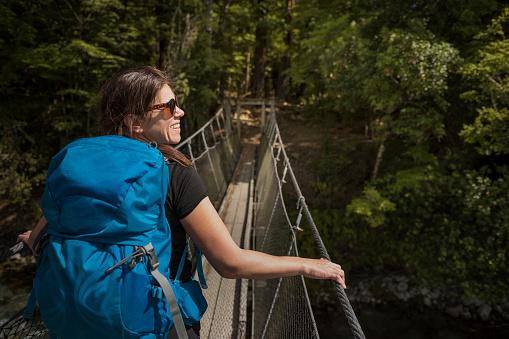 Woman walking through hanging bridge - gettyimageskorea
