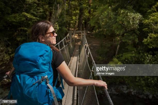 Woman walking through hanging bridge