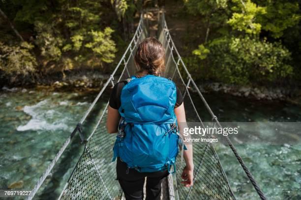 woman walking through hanging bridge - rucksack stock pictures, royalty-free photos & images
