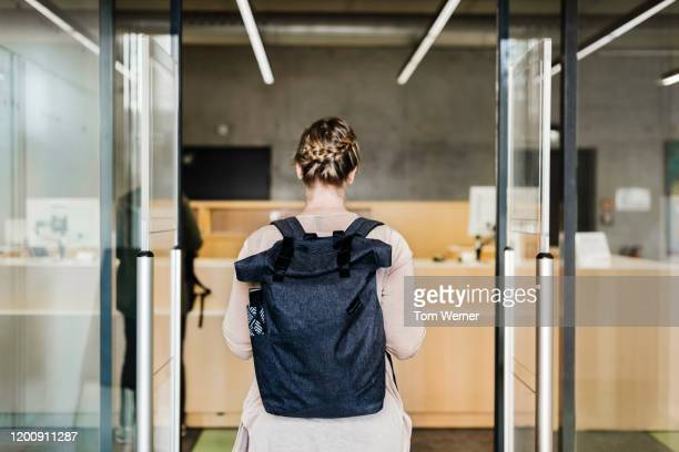 woman walking through library entrance - education stock pictures, royalty-free photos & images