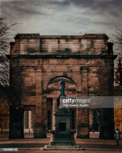woman walking through mclennan arch at glasgow green in autumn/fall - old glasgow stock pictures, royalty-free photos & images