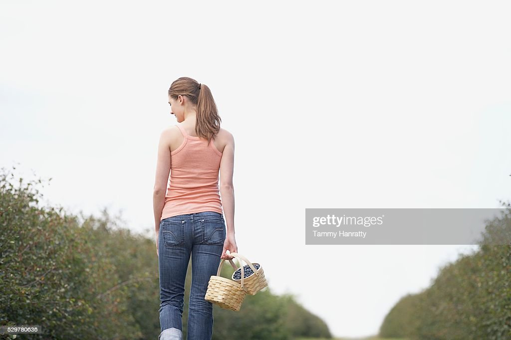 Woman walking through orchard : Foto stock