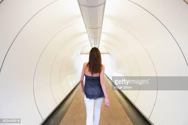 woman walking through underpass, singapore - hugh sitton stockfoto's en -beelden