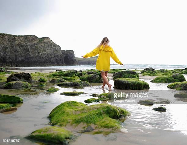 Woman walking through water on rocky coastline