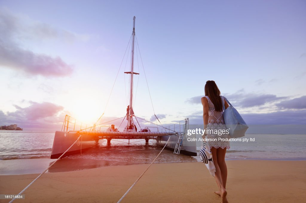 Woman walking to boat on beach : Stock Photo