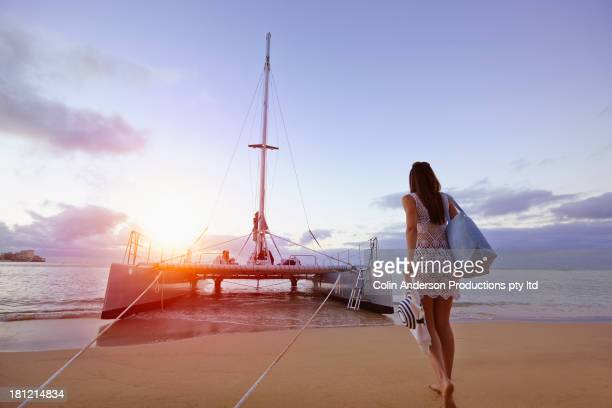 woman walking to boat on beach - catamaran stock photos and pictures