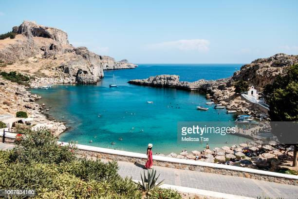 woman walking to saint paul's bay in lindos, greece - lindos stock photos and pictures