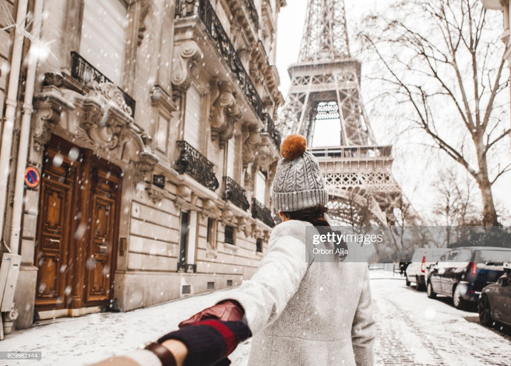 Woman walking to the Eiffel tower with snow : Stock Photo